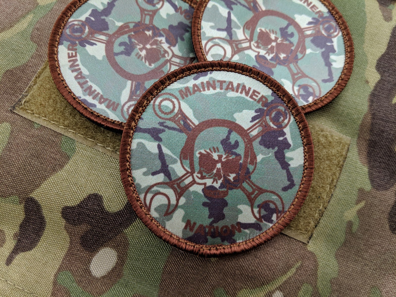 Three Maintainer Nation OCP Dye-Sublimated Morale Patches from Challenge Coin Nation on a camo fabric background