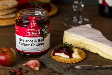 An open jar of Cumbrian Delights Beetroot and Bell Pepper Chutney, on a table next to a wedge of brie and a cracker with both brie and chutney on top
