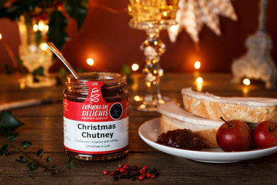 Picture of an open jar of Cumbrian Delights Christmas Chutney with the handle of a spoon emerging from the top. The jar is on a wooden table next to a white plate containing slices of bread and turkey, fruit, and a dollop of rich, red chutney. In the background are out of focus Christmas decorations.