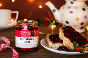 An open jar of Cumbrian Delights Christmas Jam sitting on a wooden table, next to a plate of toast spread with the rich purple jam