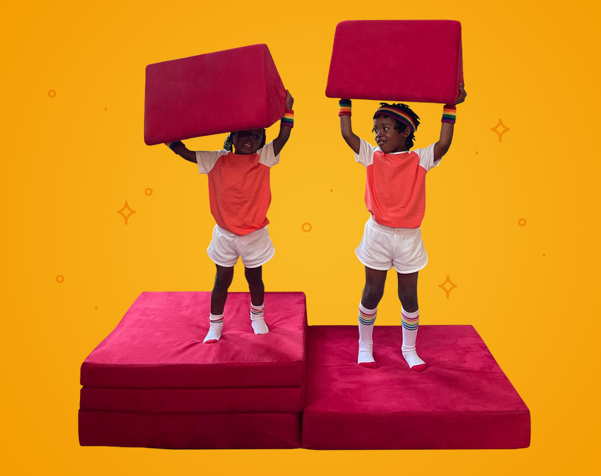 Two children standing on Nugget cushions, holding pillows overhead like weightlifters