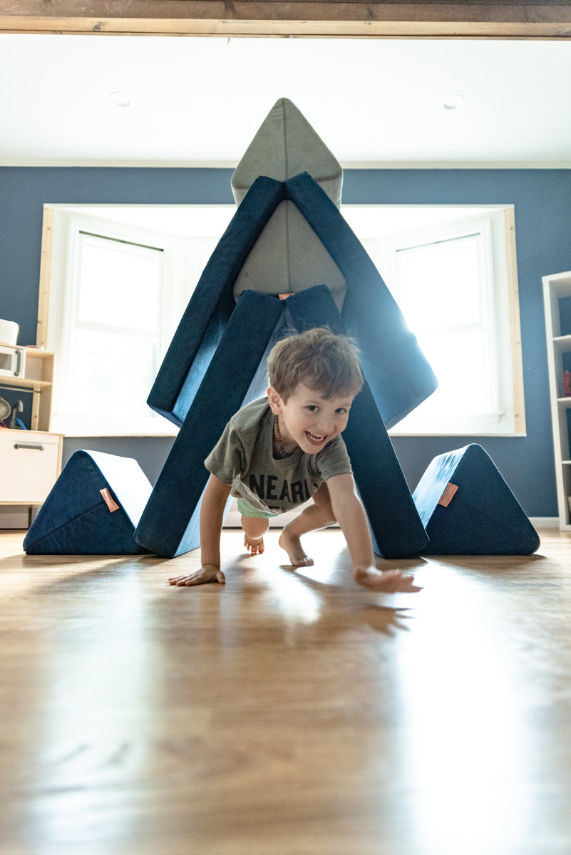 Child crawling toward the camera, out of a Nugget fort