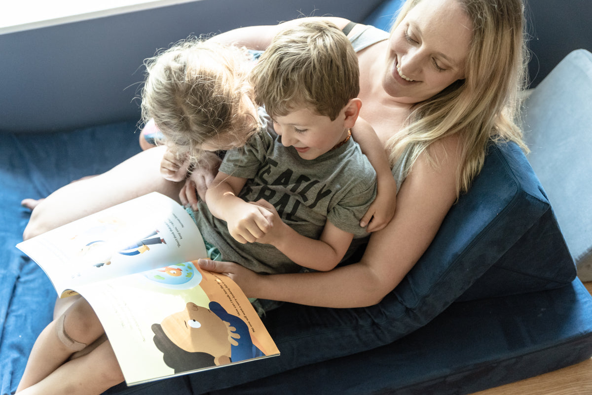 Adult and two children sitting on a Nugget, reading a story together