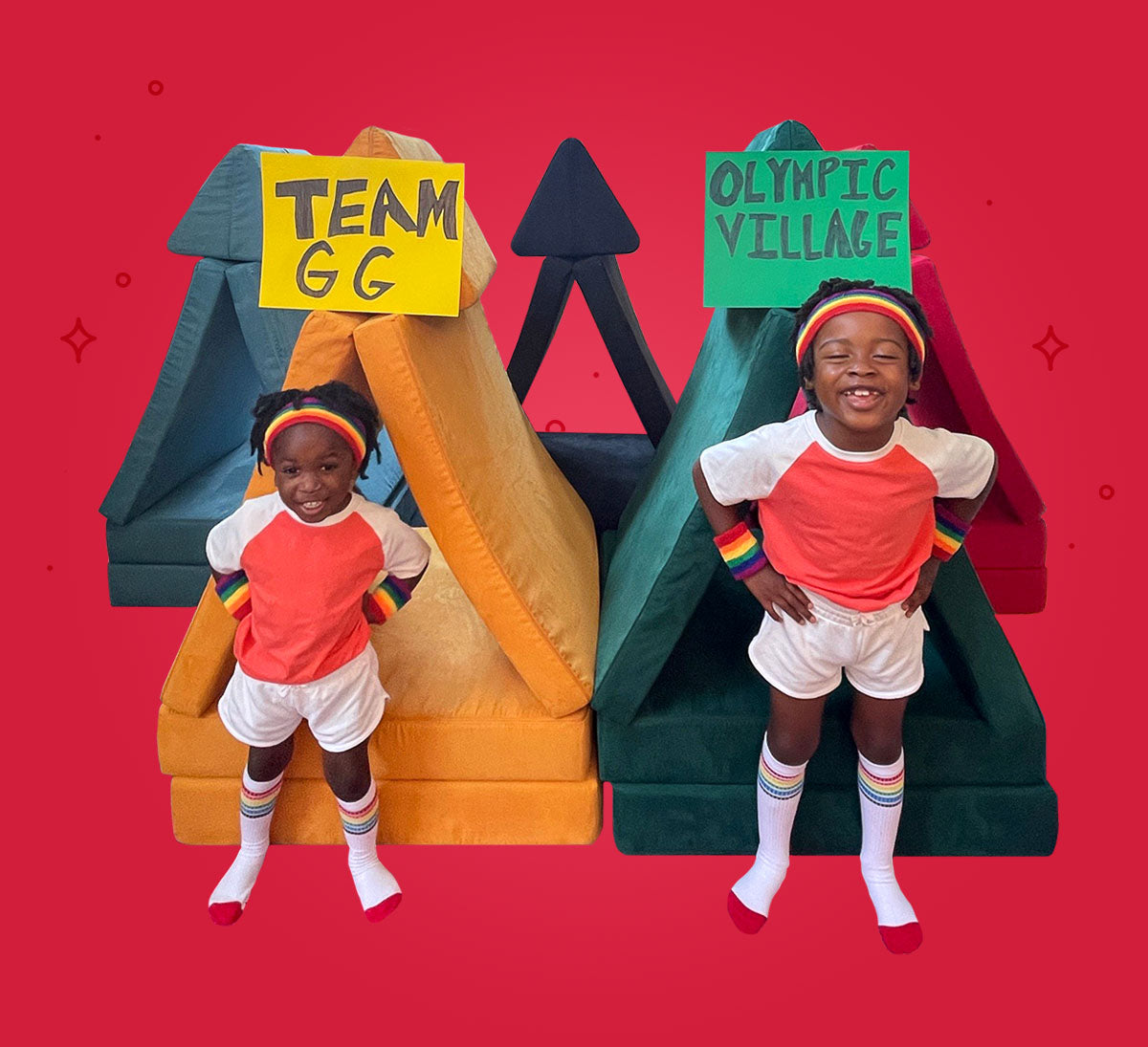 """Two children posing proudly in front of tented Nugget couches, one with a sign """"Team GG"""" and one with a sign """"Olympic Village"""""""
