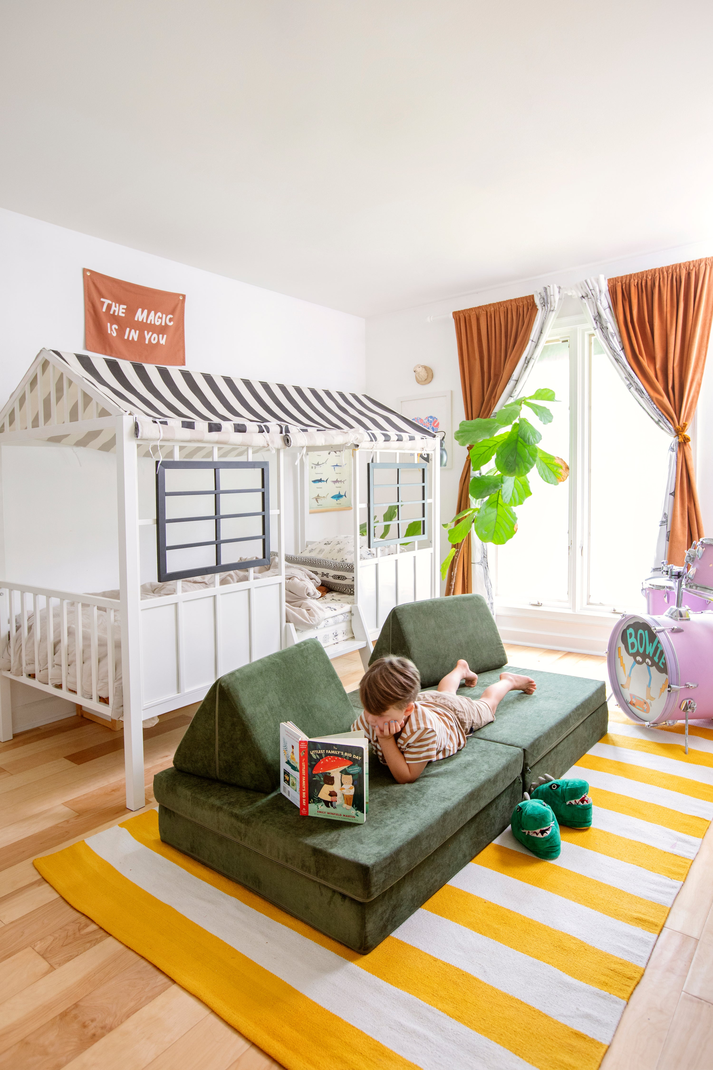 Kid lounging on a Willow Nugget reading a book. Room has a house bed, striped yellow and cream rug, and drum set in right corner