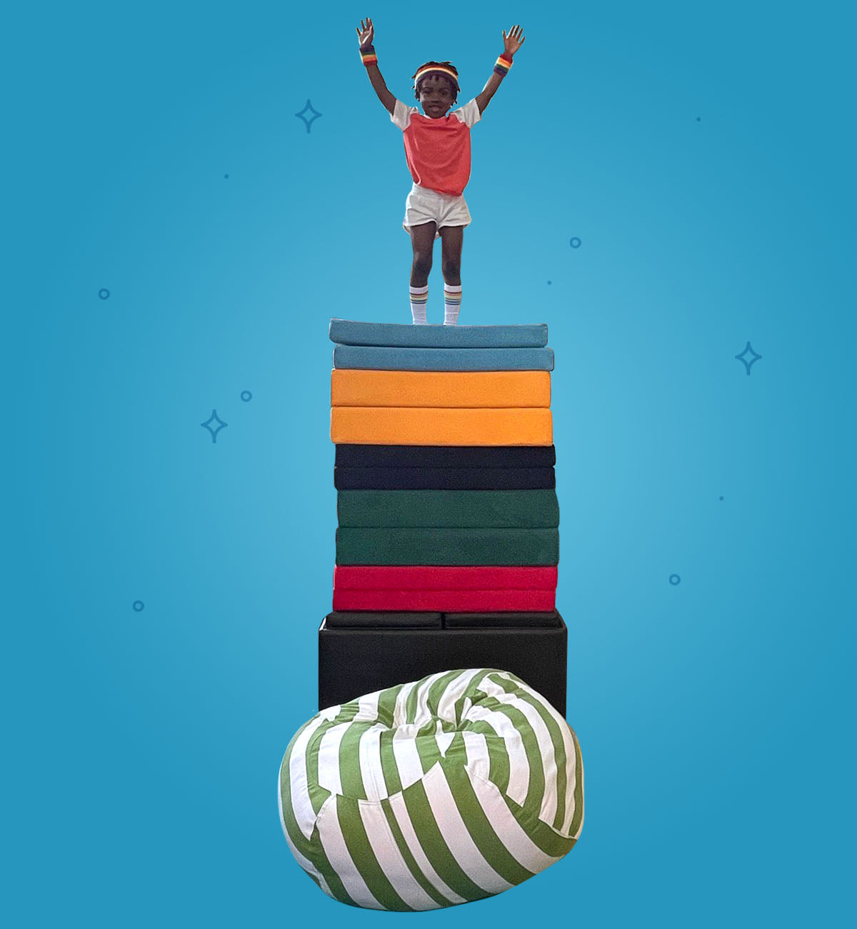 Child saluting on top of large stack of Nugget bases and cushions, with a large pouf placed at base of stack