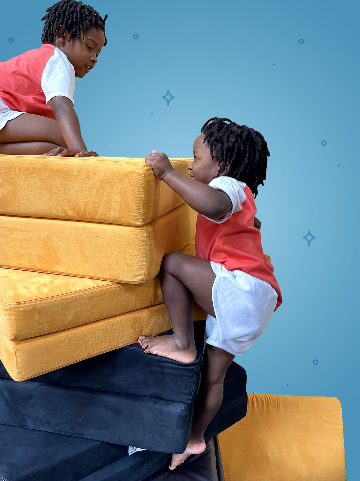One child perched on top of a stack of cushions, looking down at other child who is climbing up the stack like a rock climber