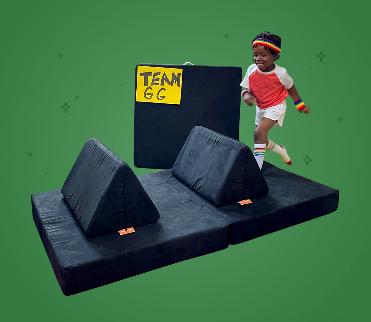Child leaping over a pillow placed on cushion, set up like a hurdle from track and field
