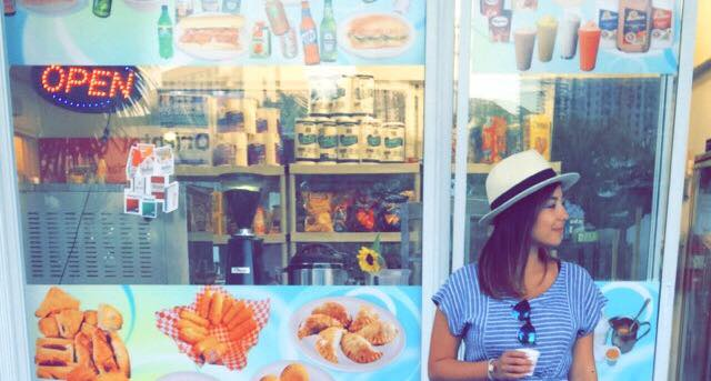 Hannah at a food stand, looking off camera and holding a coffee in hand