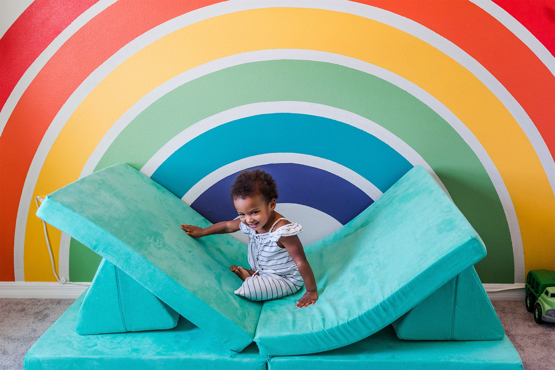 Young toddler playing on Cactus Nugget couch in front of bright rainbow mural on wall