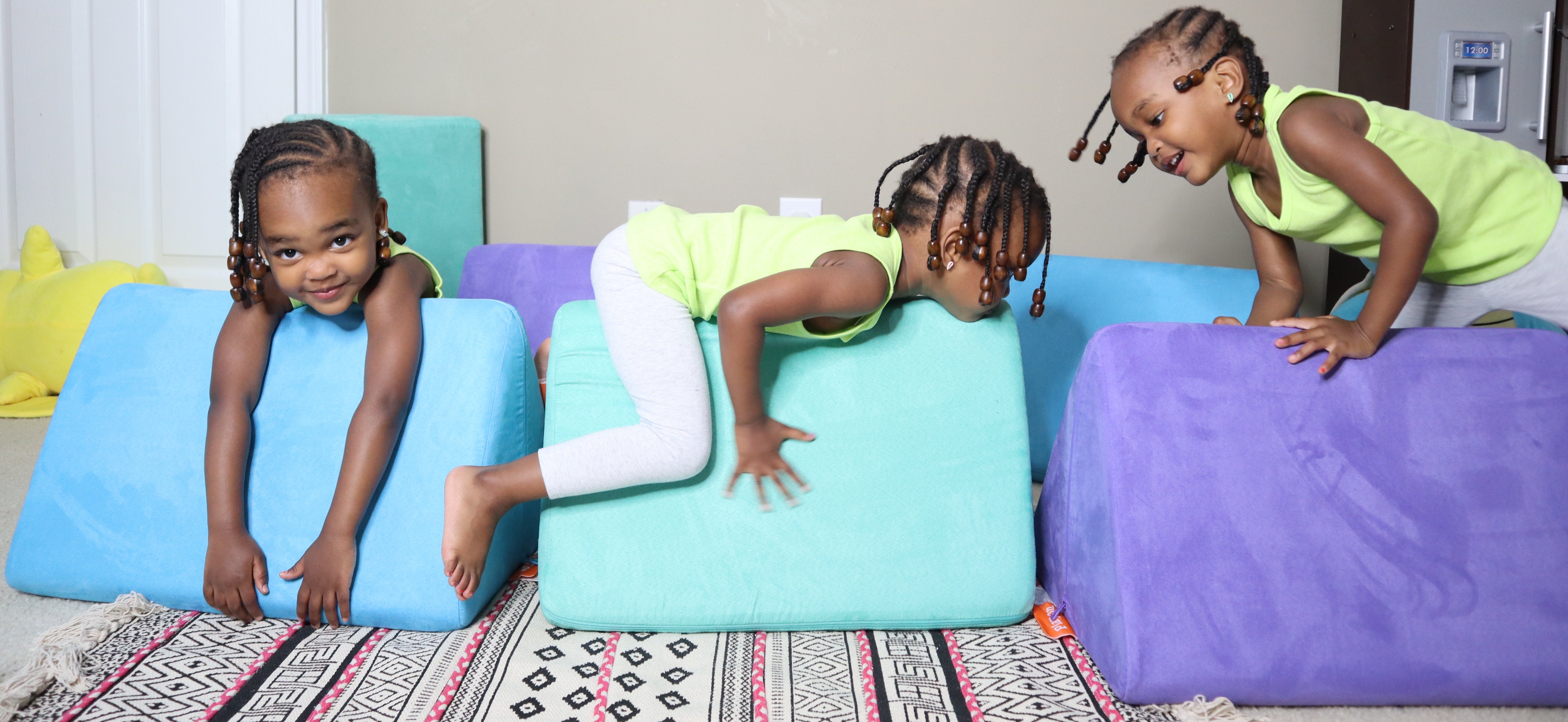 Three young girls playing on Nugget pillows: Snorkel, Cactus and Potion colors from left to right