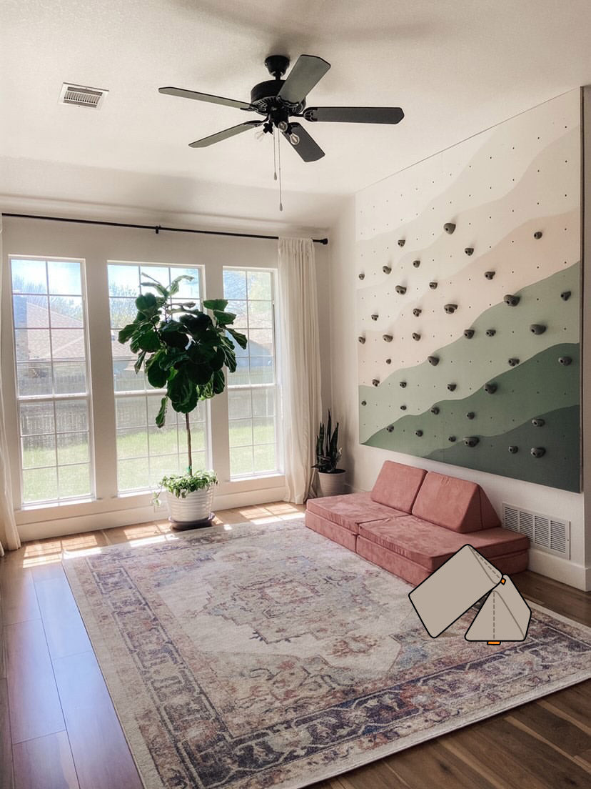 Sun-filled room featuring a Sweetpea couch, rock wall, rug, large houseplant, and added Pebble pillows illustration