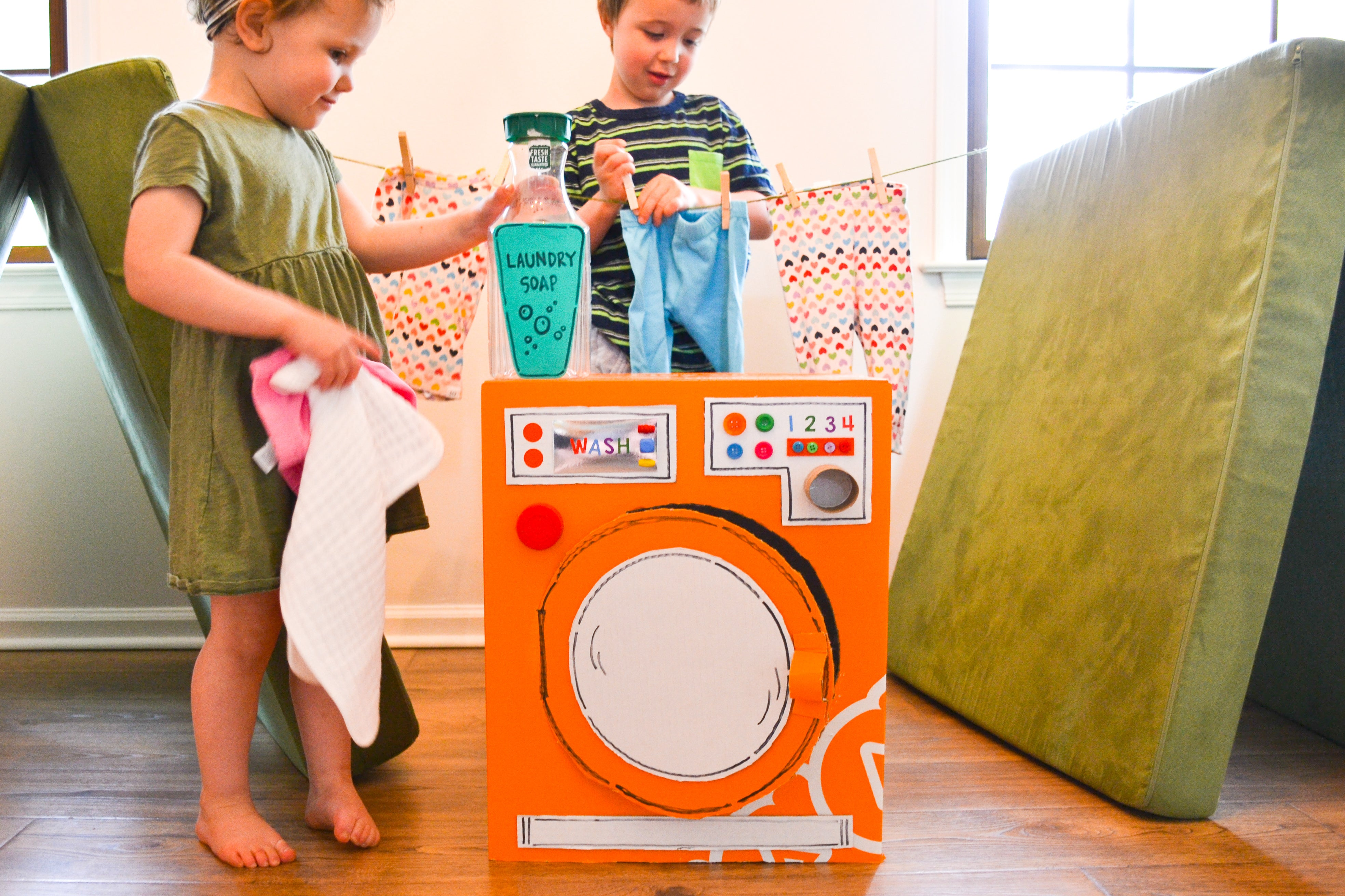 Two children playing with play washing machine made from Nugget Big Orange Box, with clothing line suspended between two Nugget pieces