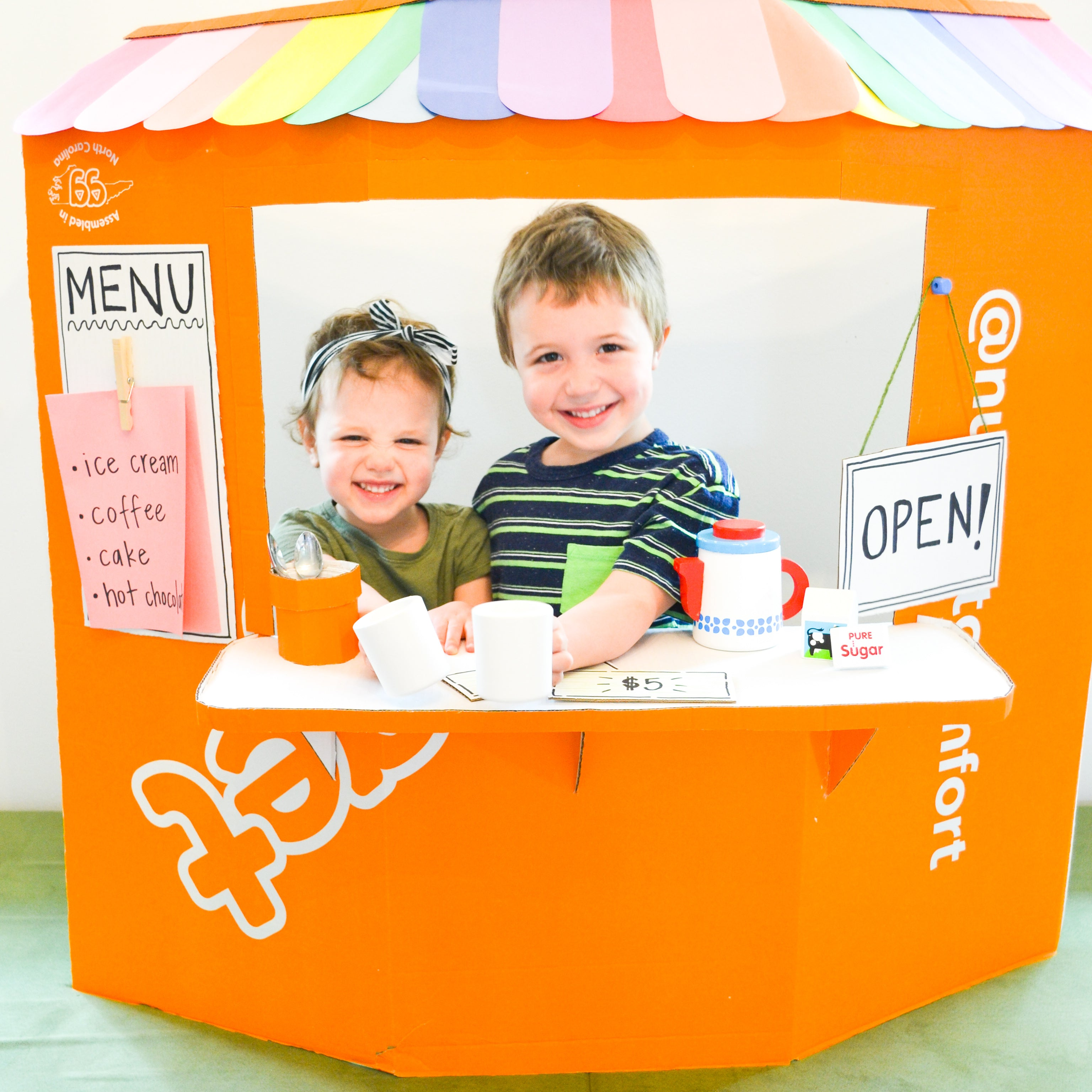 Two children grinning at camera from their play snack stand, made from Nugget Big Orange Box