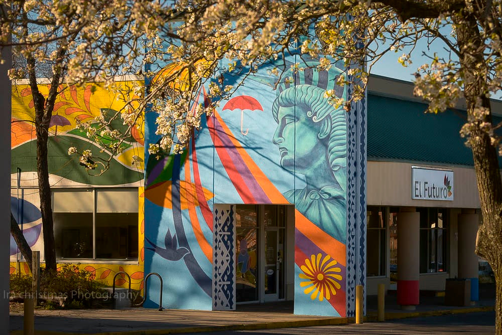 Exterior of El Futuro clinic, showcasing bright mural on side with the Statue of Liberty, a dove, and other imagery