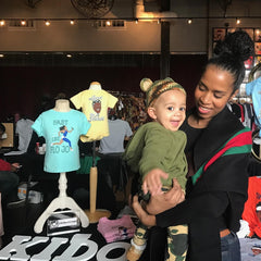 Woman holding toddler next to mannequins in store, displaying her clothing line for children