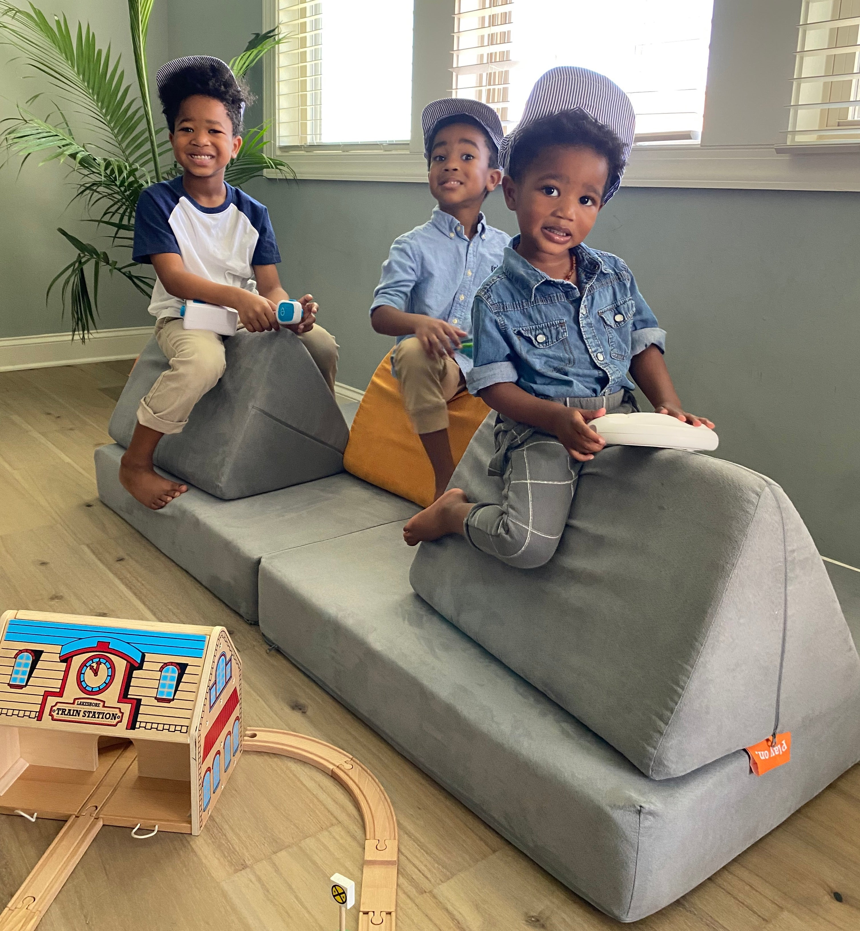 Three kids wearing train conductor hats, seated on triangular pillows in Koala color. Wooden train toys in bottom left of photo.