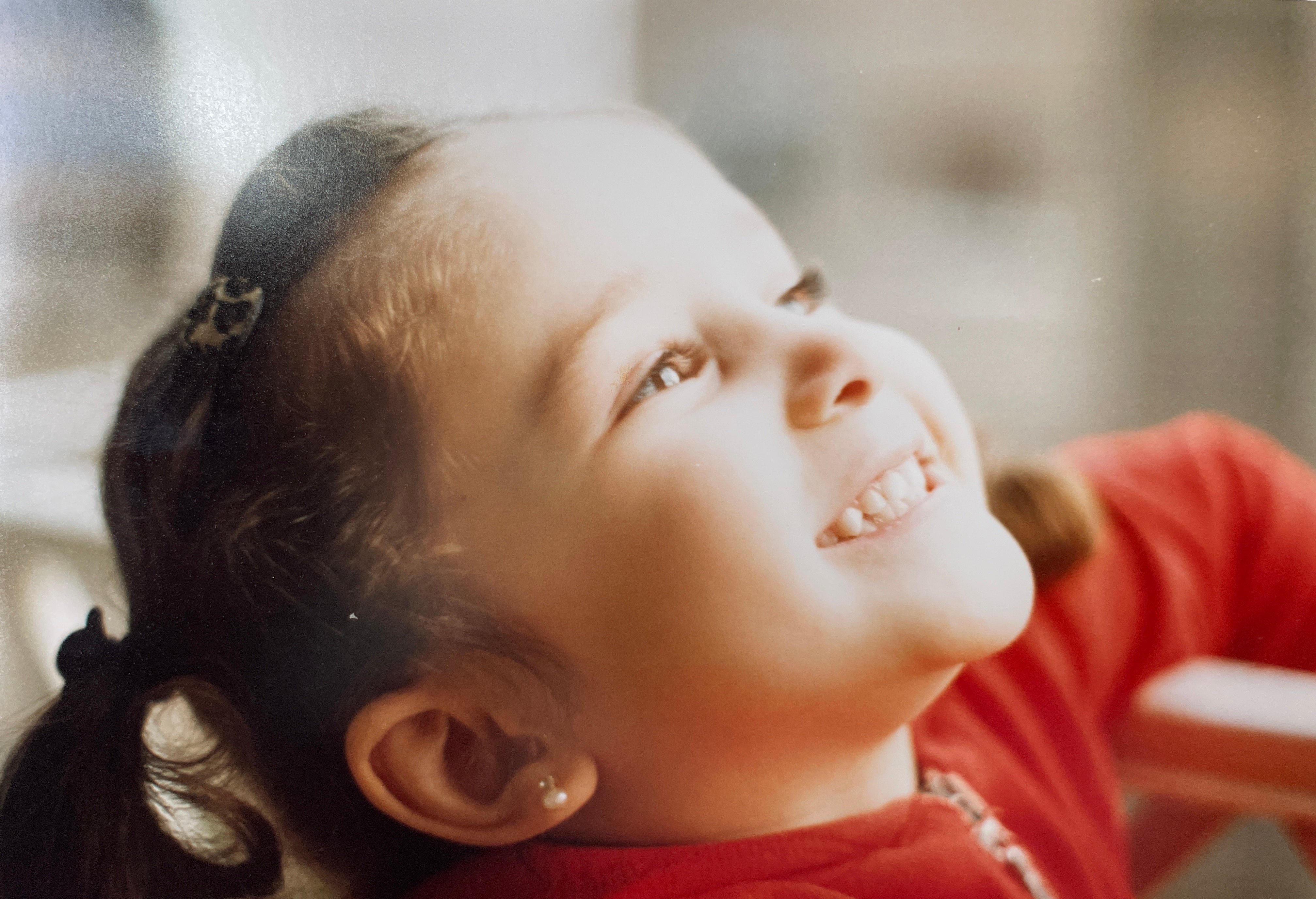 Ghenwa, Nugget Product Designer, as a young child, grinning and looking up to someone off camera