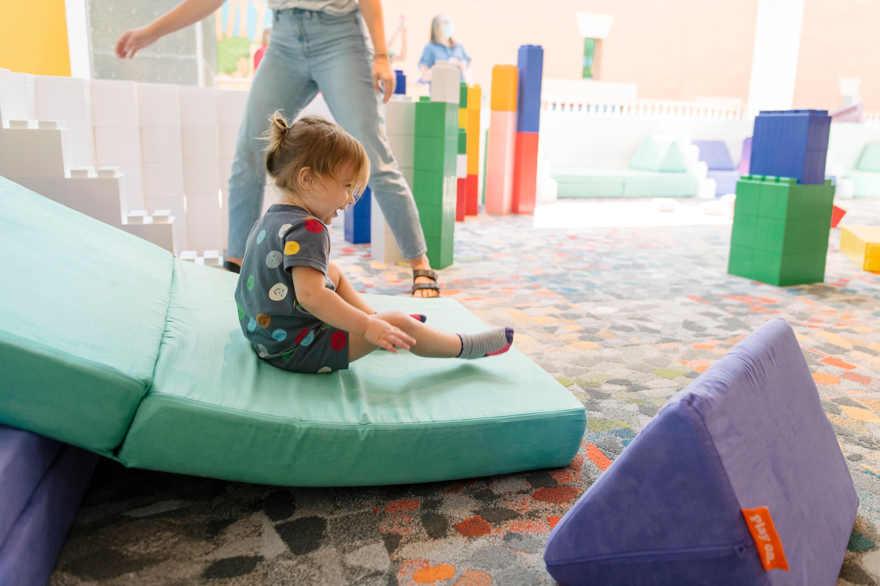 Young child sliding down a Nugget slide at imagiFAB exhibit