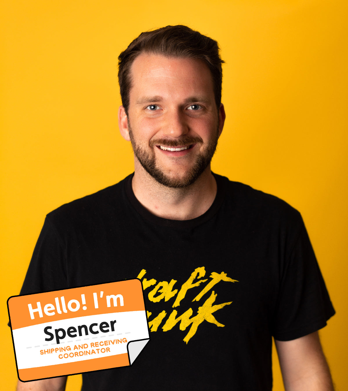 """Spencer, bearded man with short hair, smiling at camera. Name tag illustration included, stating """"Hello! I'm Spencer, Shipping and Receiving Coordinator."""""""