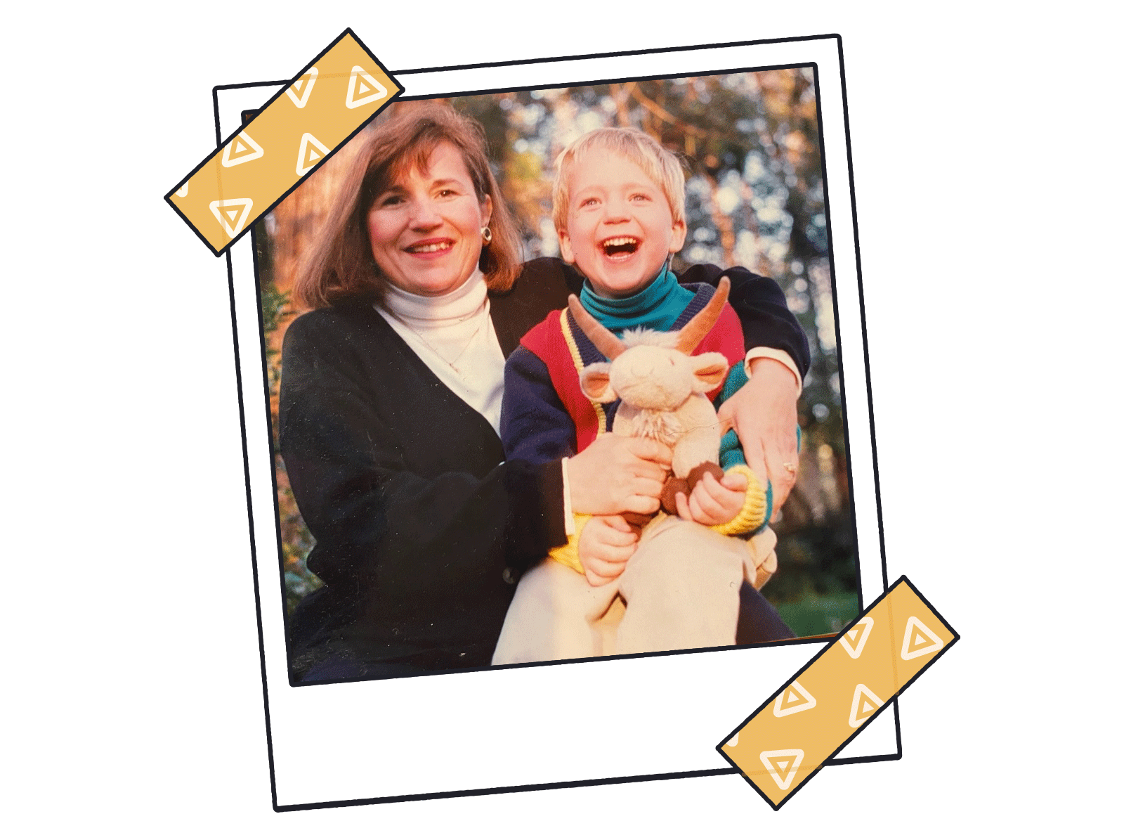 Autumn outdoor photo of mother in turtleneck and sweater with son holding stuffed animal