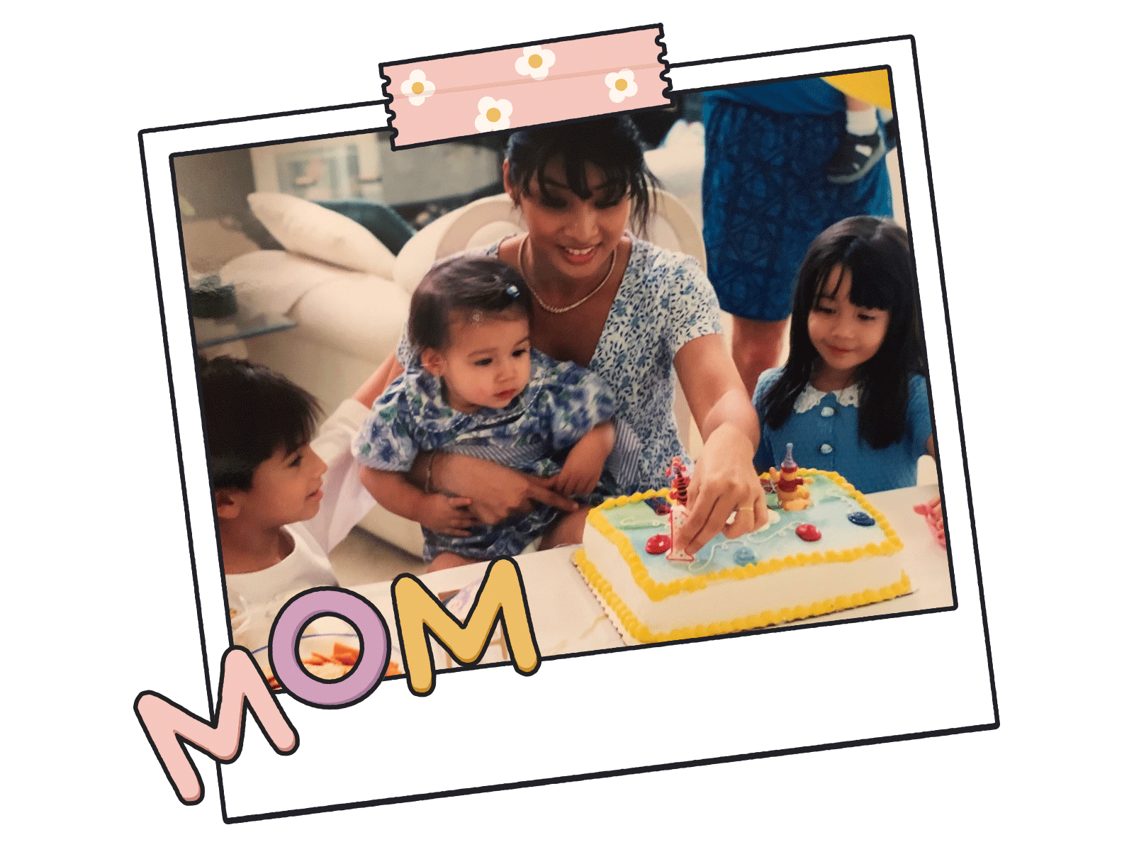 Mother seated at table with two young children and baby on her lap, at birthday celebration