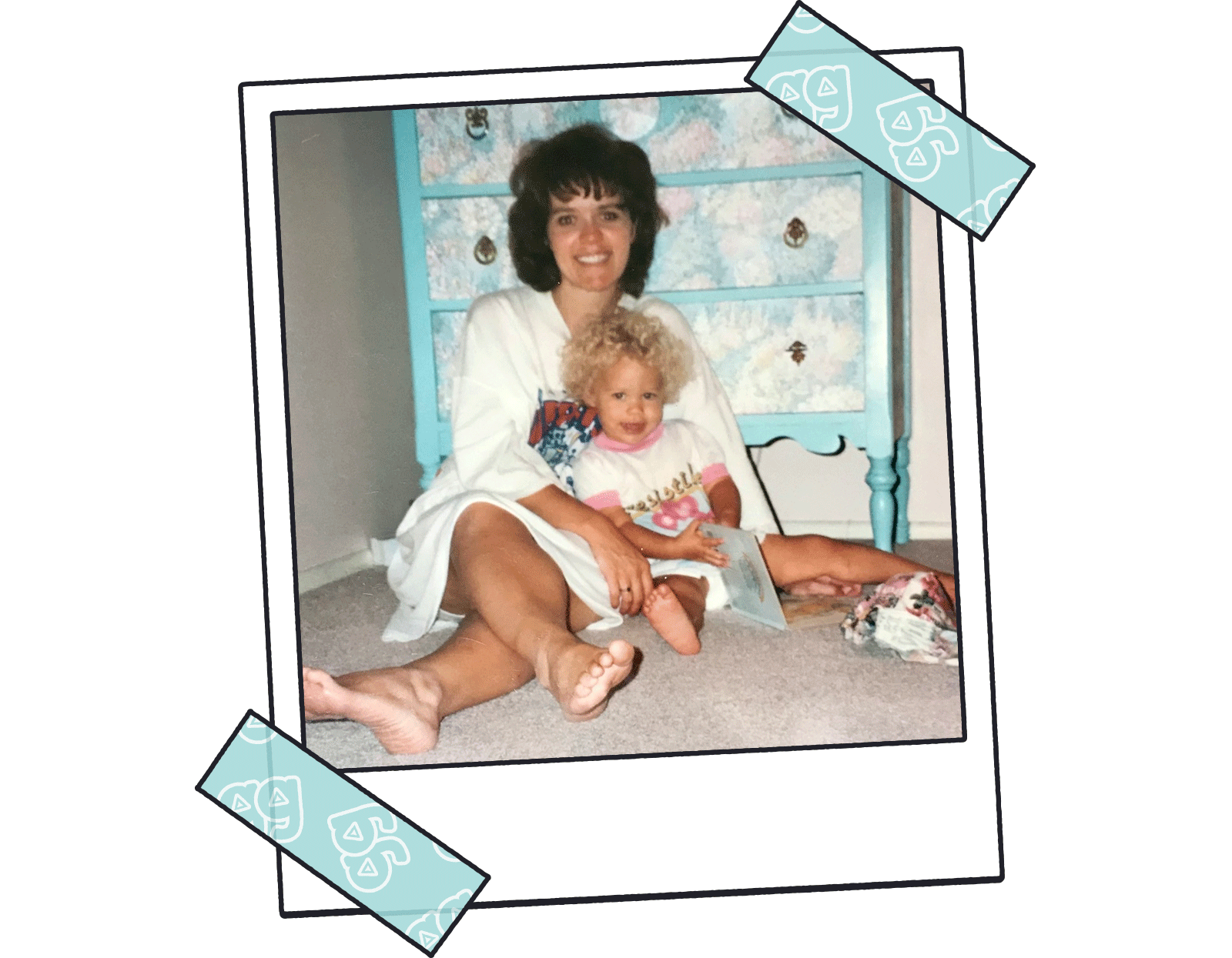 Mother in oversized t-shirt sitting with daughter on the floor in front of a floral-print dresser