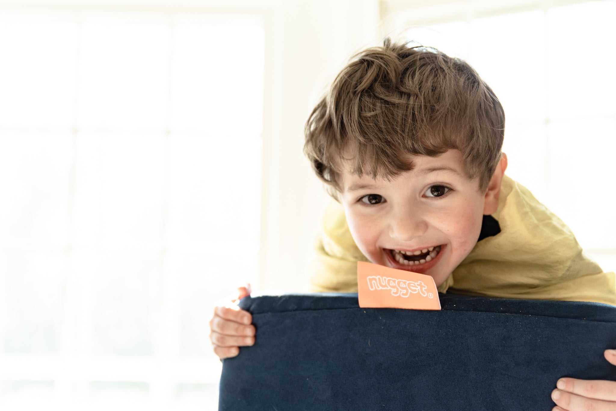 Child leans forward on a Nugget pillow, grinning at camera