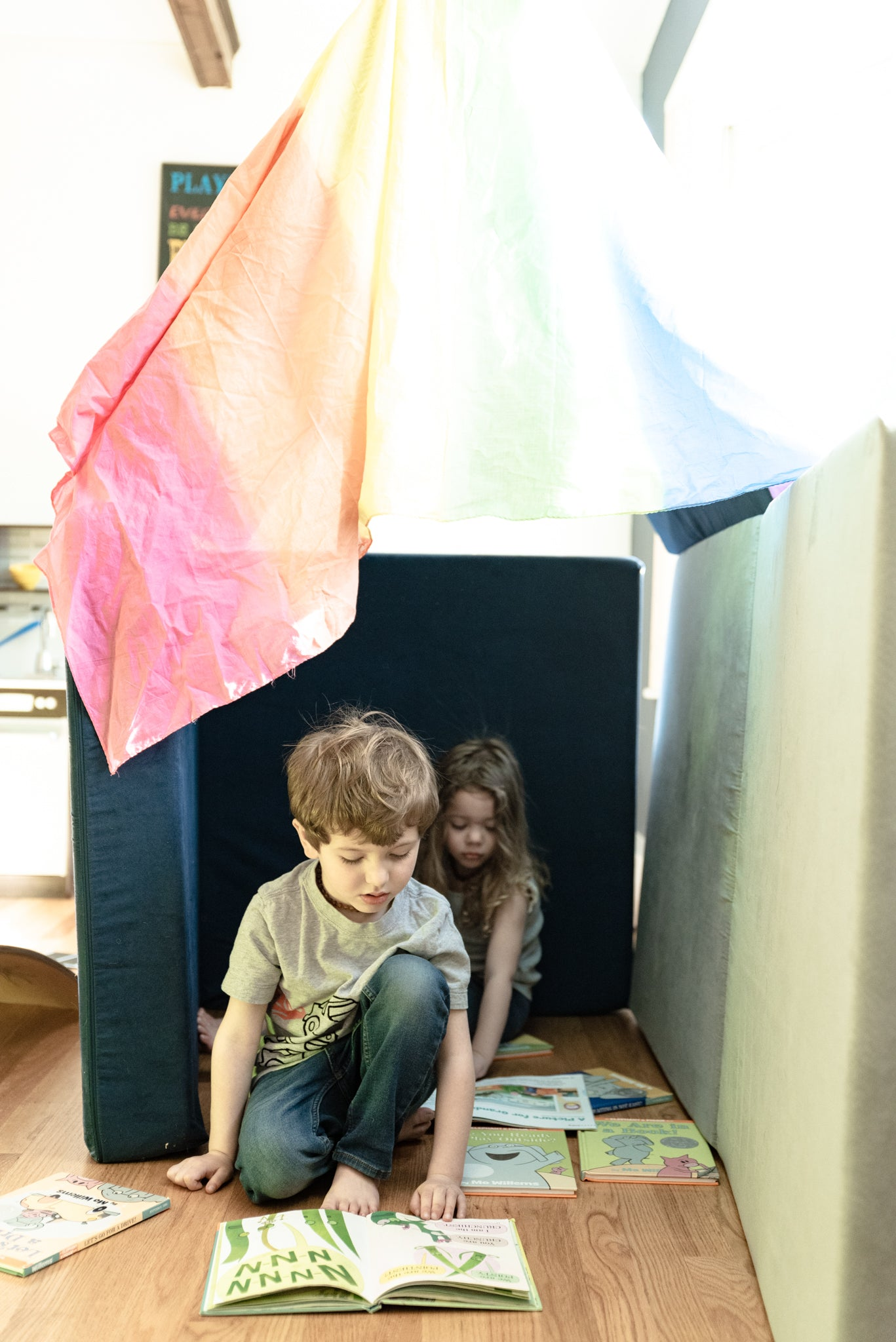 Two children reading stories in a Nugget fort, made with a play silk as the roof