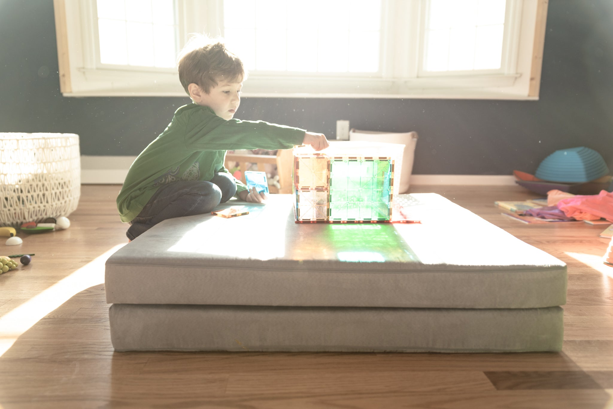 Child kneeling by folded Nugget cushion, reaching for magnetic tiles placed on cushion