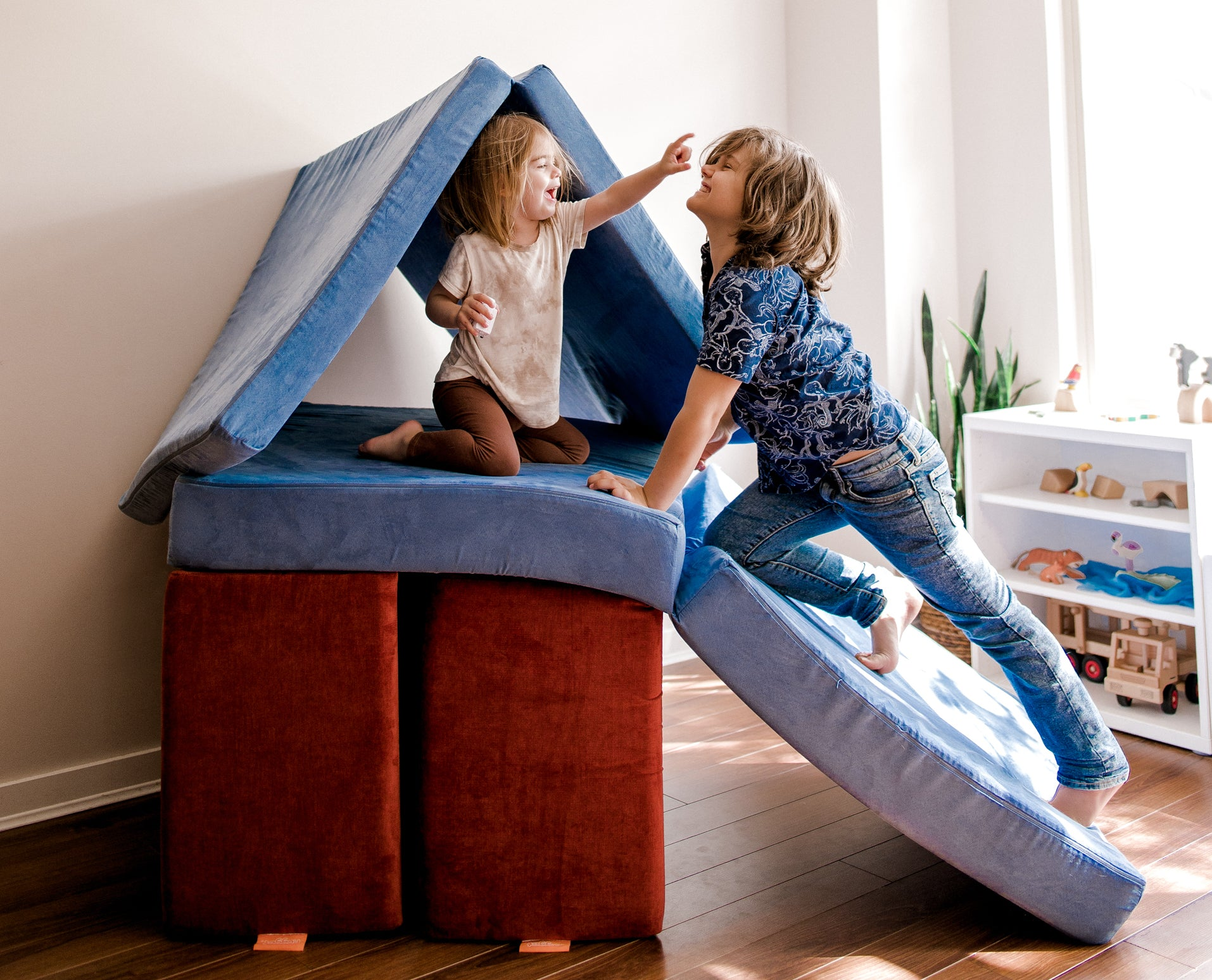 One child sits in a Redwood and Bluejean Nugget fort, older sibling climbs up ramp on hands and knees