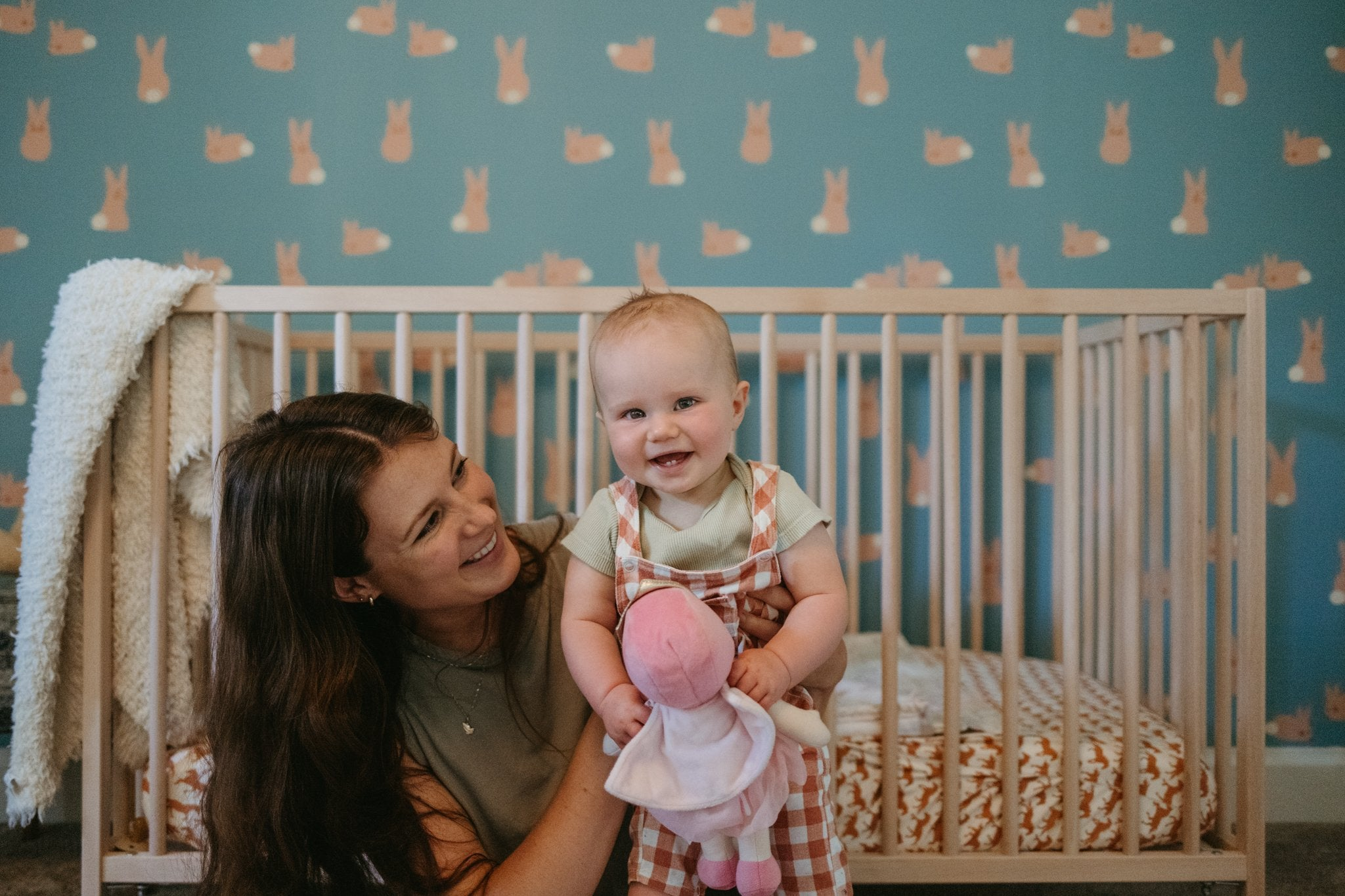 Richele smiling at and holding her daughter in her nursery, featuring bunny Anewall wallpaper