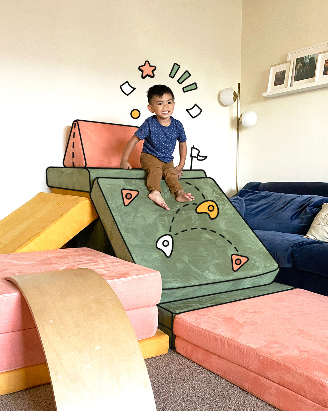 Child sitting at top of three Nugget build slide, with drawn on rock climbing holds on the incline area