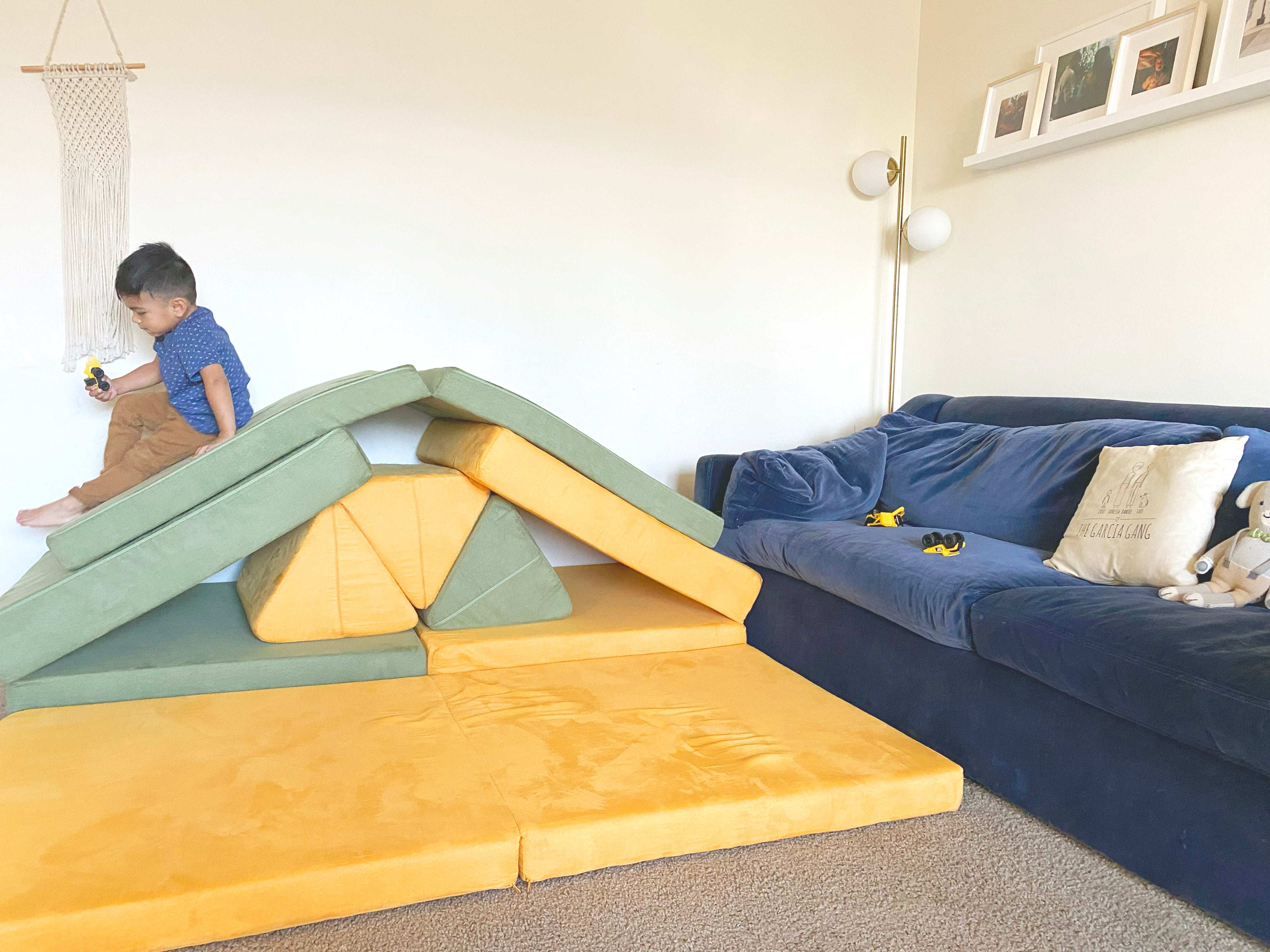 Child sliding down a two Nugget build, with a cushion placed over top of two ramp bases and pillows