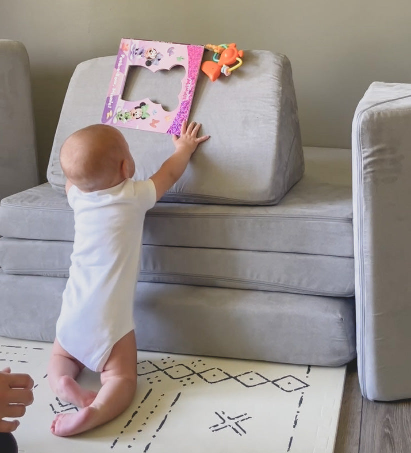 Baby kneeling and reaching for toy placed on Nugget