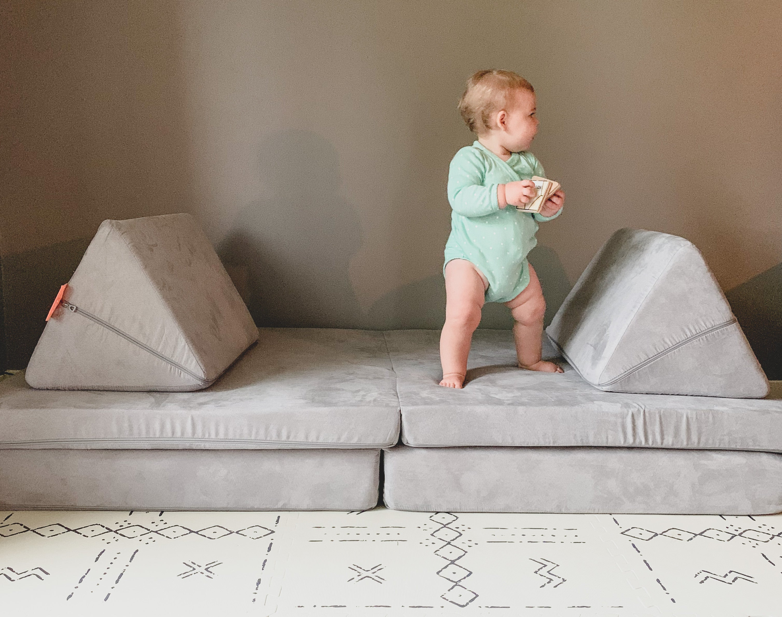 Baby walking on Nugget between pillows