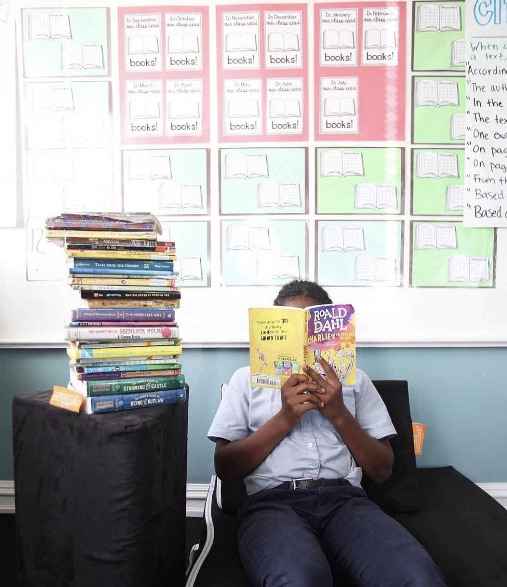 Student sitting on a Nugget, reading a book, with a stack of books next to them placed on top of a Nugget pillow