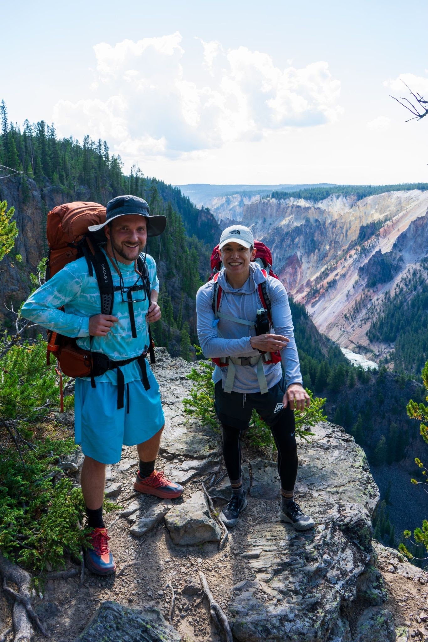 Two adults dressed in hiking clothes, wearing hiking packs, on a trail in Grand Tetons National Park