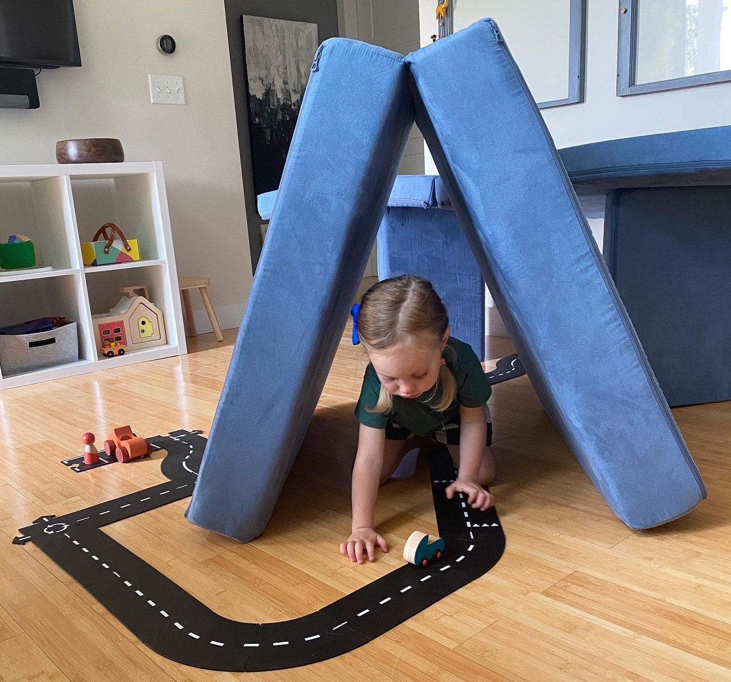 Child playing with a toy car on a toy road that goes from a parking lot, through a Nugget tunnel made by a folded over cushion and into a Nugget garage, made by stacking a flat cushion on top of two pillow pillars.