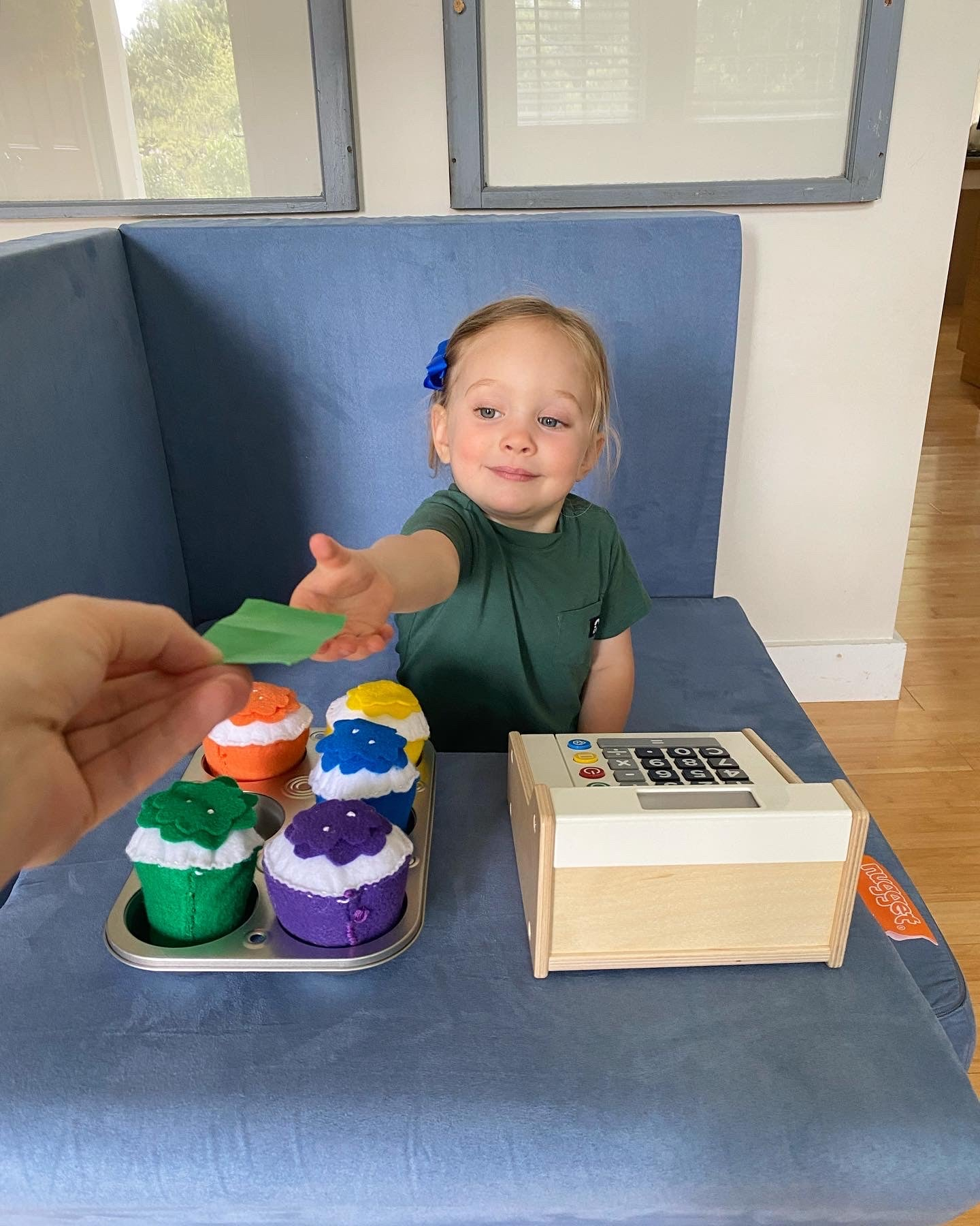 """Child reaching for play money from a """"customer"""" at her cupcake stand, made with a Nugget and a toy cash register and plush cupcakes"""