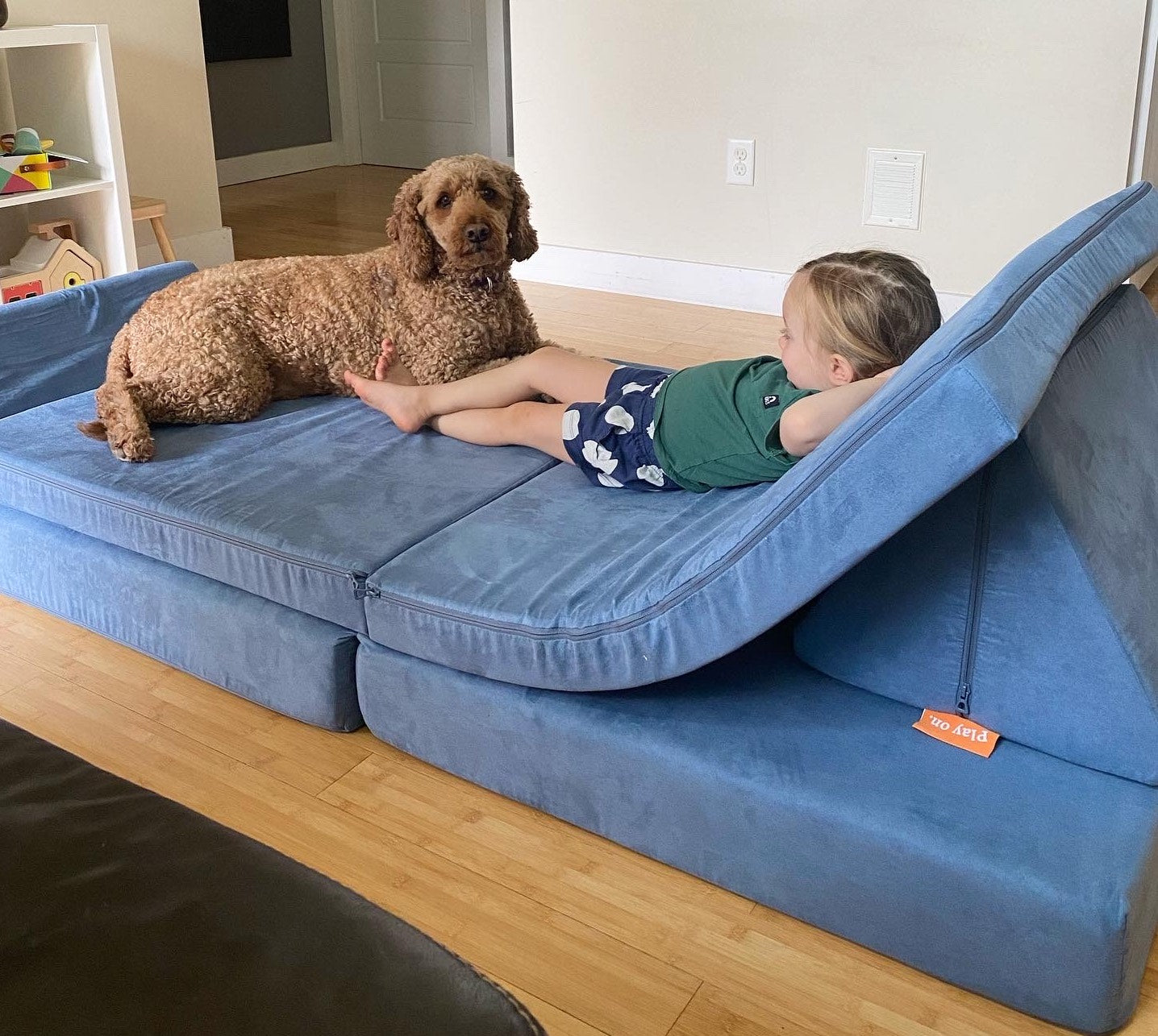 Child and dog lounging on a Nugget together
