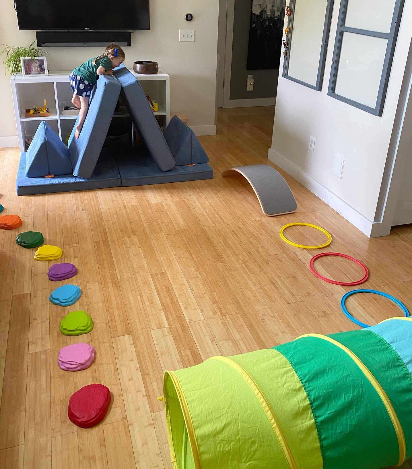 Child climbing up a Nugget base folded in two like a mountain peak, with a tunnel, stepping stones, and hula hoops set up around as an obstacle course