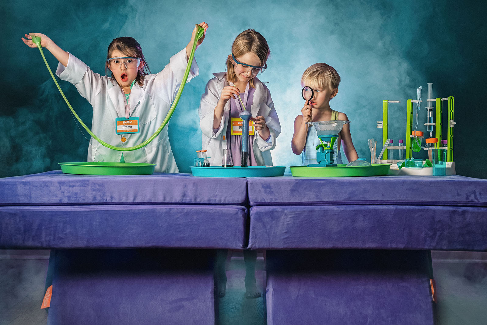 Three kids dressed as scientists, experimenting at their lab table made of a Potion Nugget couch