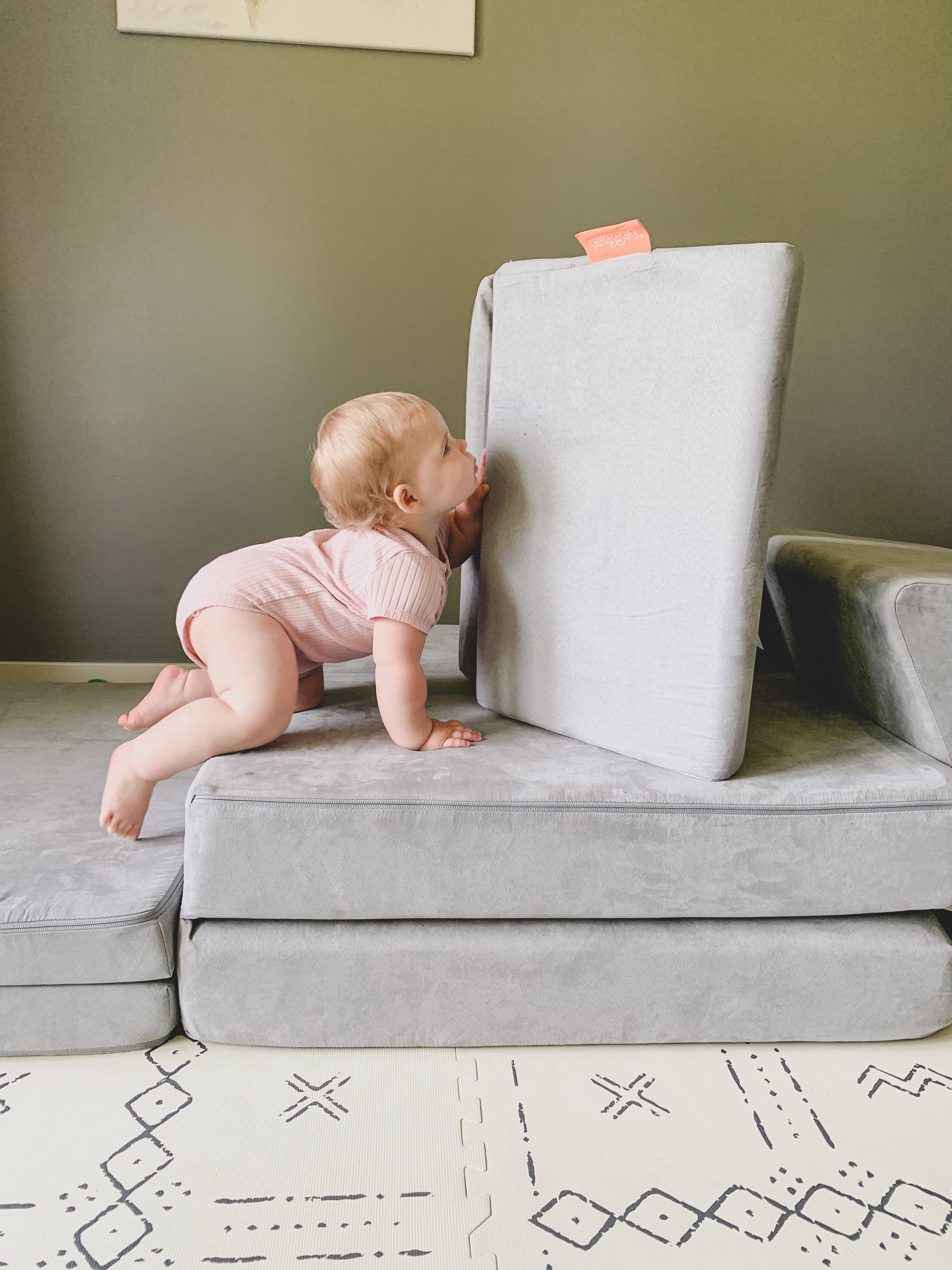 Baby crawling up Nugget cushions at different heights