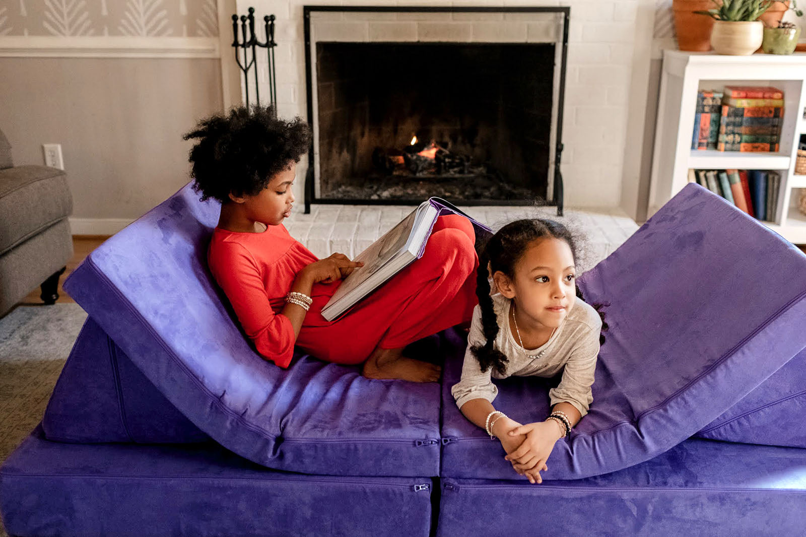 Two children lounging on Potion Nugget couch in front of fireplace