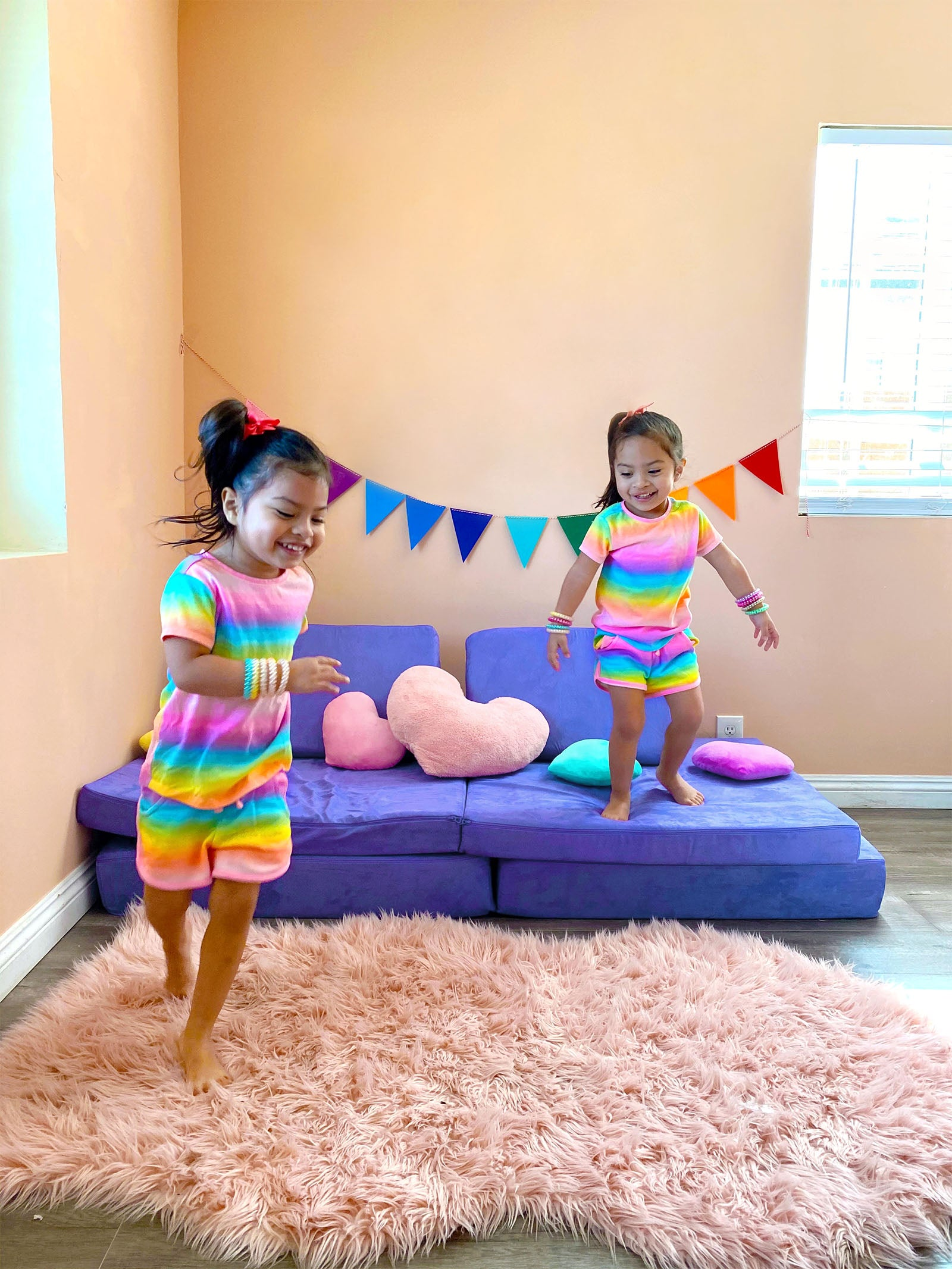 Twins playing with Potion Nugget couch, one running on pink carpet, one standing on couch