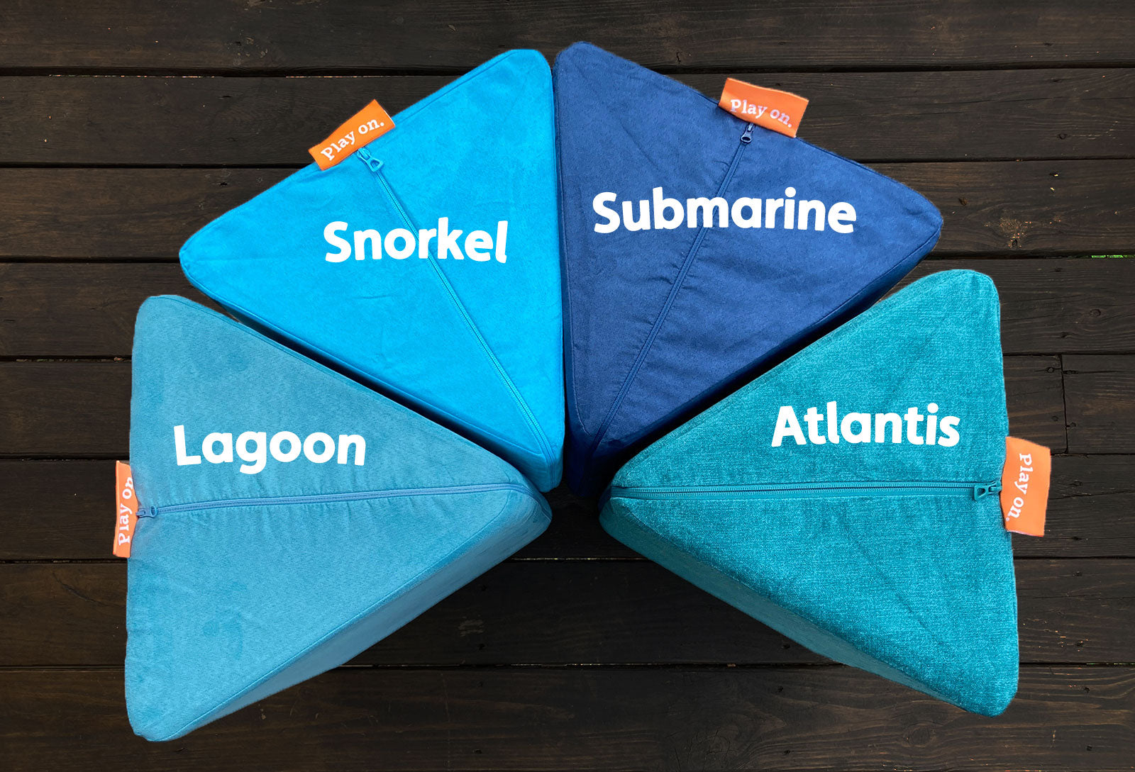 Four Nugget pillows, in different shades of blue: dusty, desaturated warm blue; bright, popping aquamarine; deep, nautical navy; and a textured teal blue