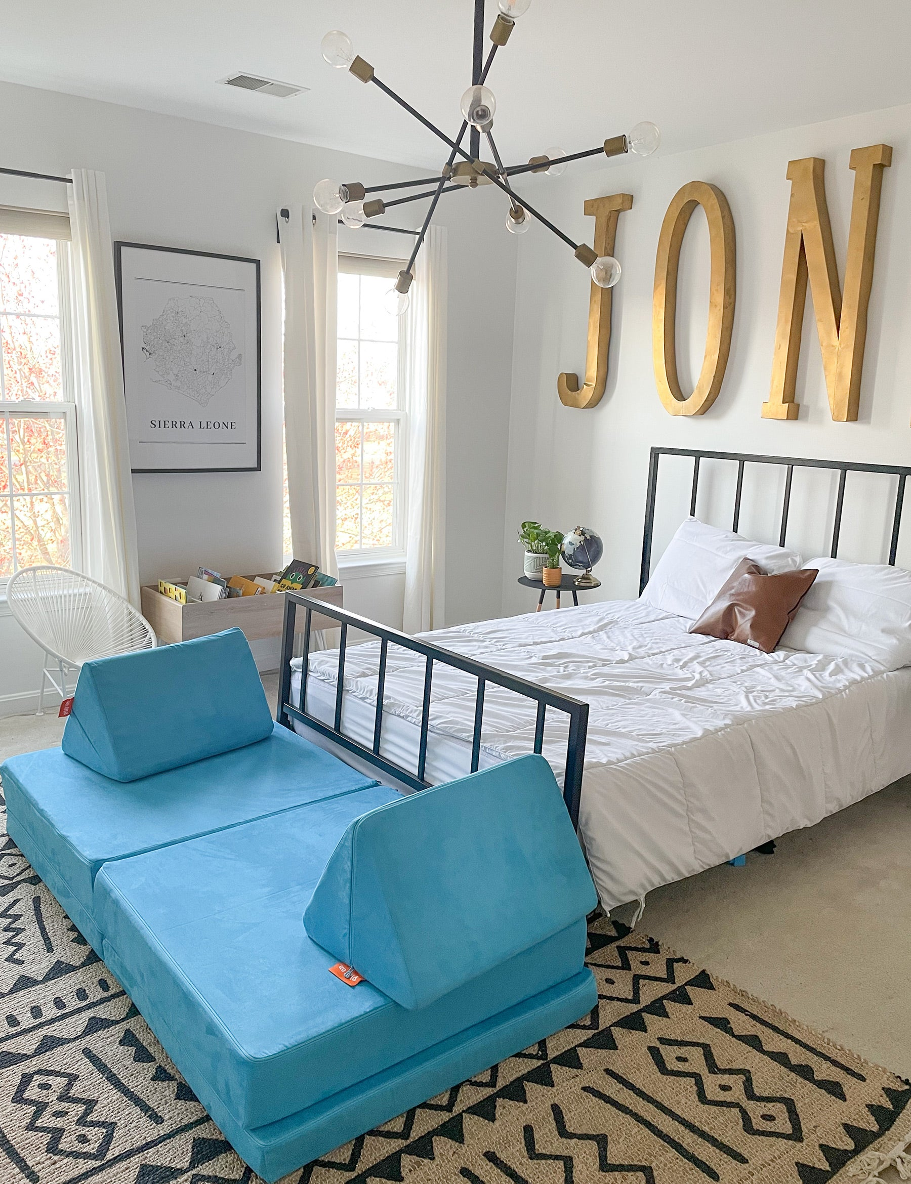 Bright, aquamarine-toned Nugget couch at the foot of a bed in a well-lit, white-walled bedroom with gold accents