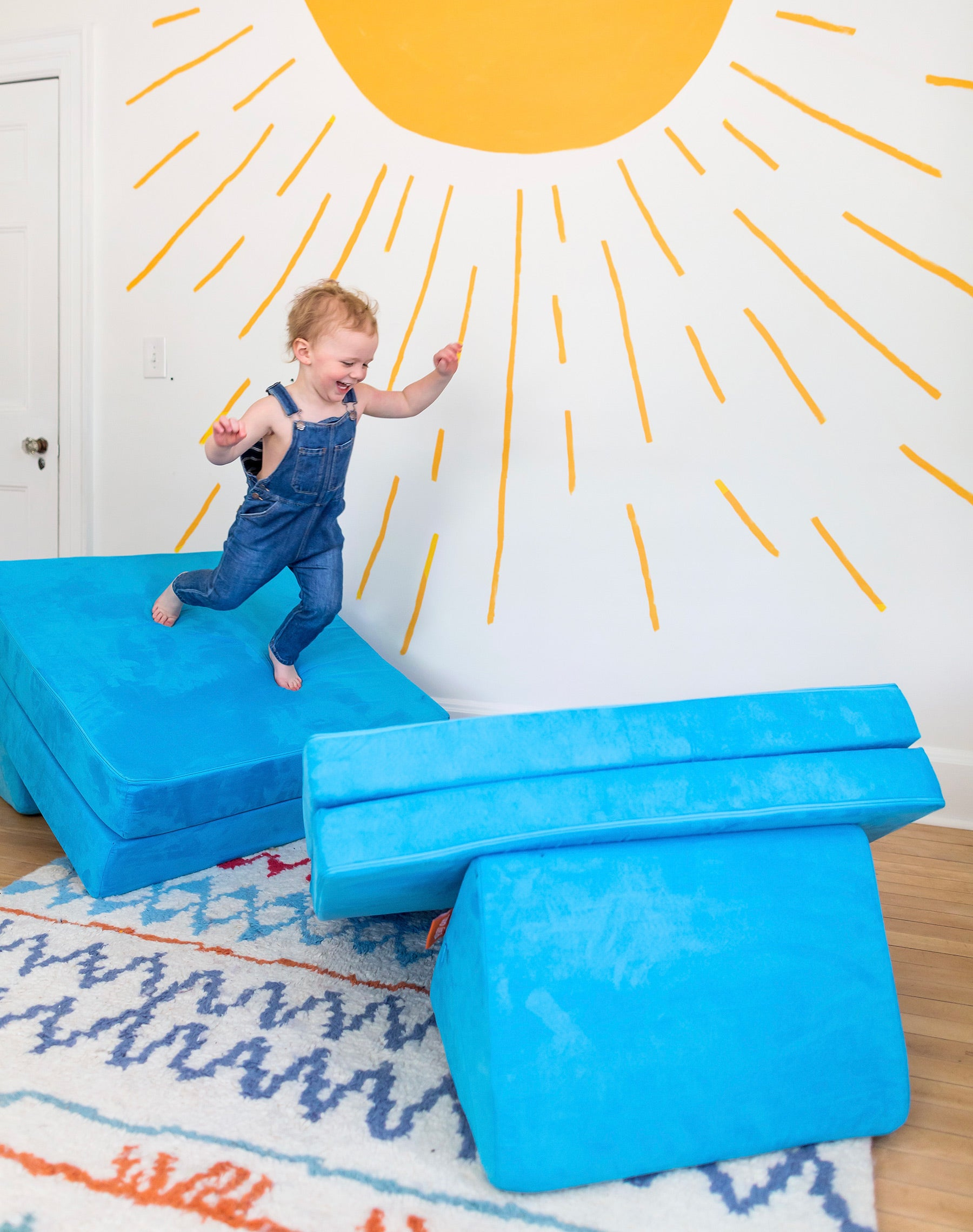Toddler jumping between two pieces of aquamarine-colored Nugget, in front of bright yellow sunshine mural