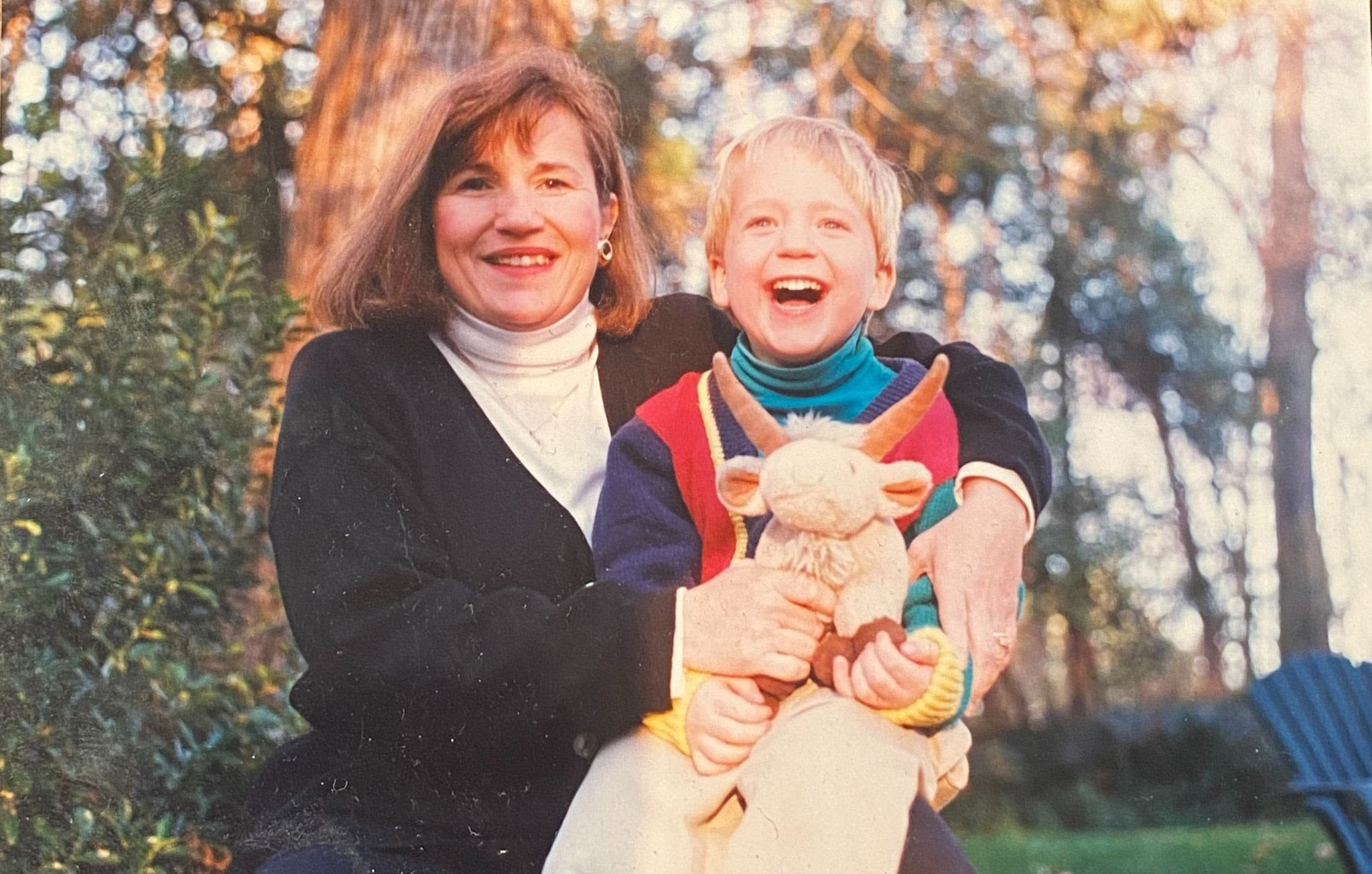 Little kid Spencer sitting on his mom's lap, facing camera with a big smile on his face